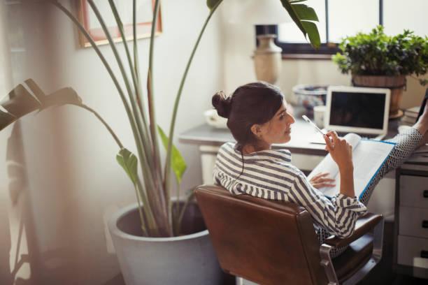 Femme qui travaille à domicile avec les pieds sur son bureau