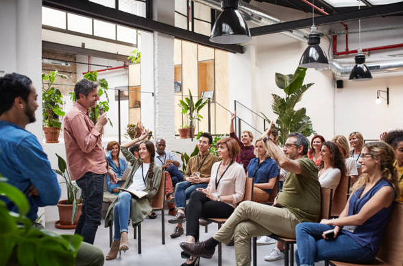 Réunion d'entreprise avec des salariés souriants et un cadre qui fait un discours