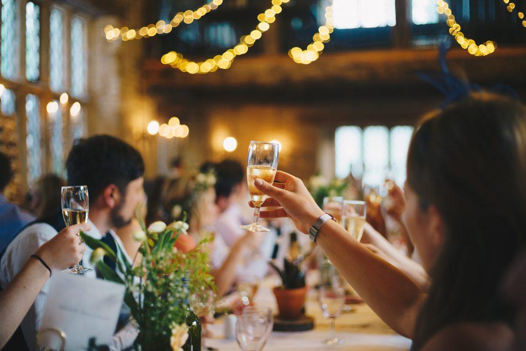 Salle de fête avec invités qui lèvent leur coupe de champagne