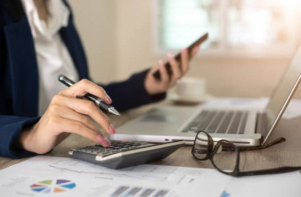 Femme qui tient les comptes d'une entreprises à l'aide d'une calculette