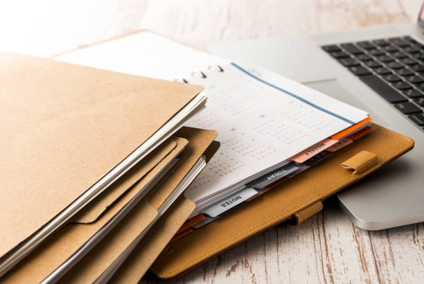 Pile de dossiers et ordinateur portable sur un bureau