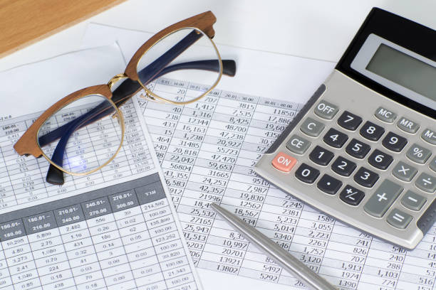 Documents avec données financières, calculette, stylo et paire de lunettes sur un bureau