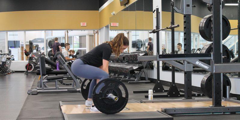 Une jeune femme en train de soulever des poids