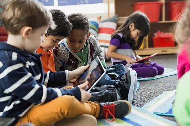 Enfants en maternelle sur des tablettes numériques