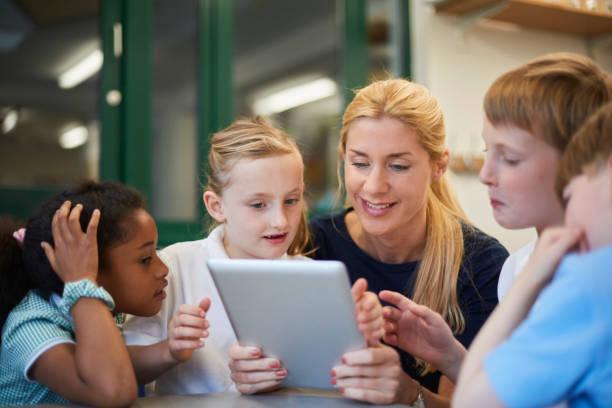 Une enseignante et un groupe d'élèves regroupés autour d'une tablette numérique