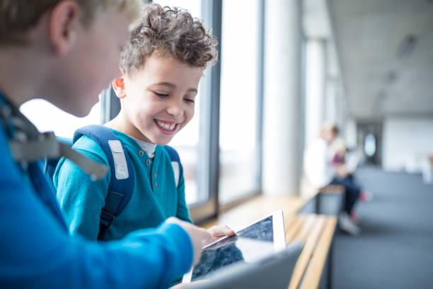 Deux enfants qui jouent sur une tablette numérique dans un couloir d'école