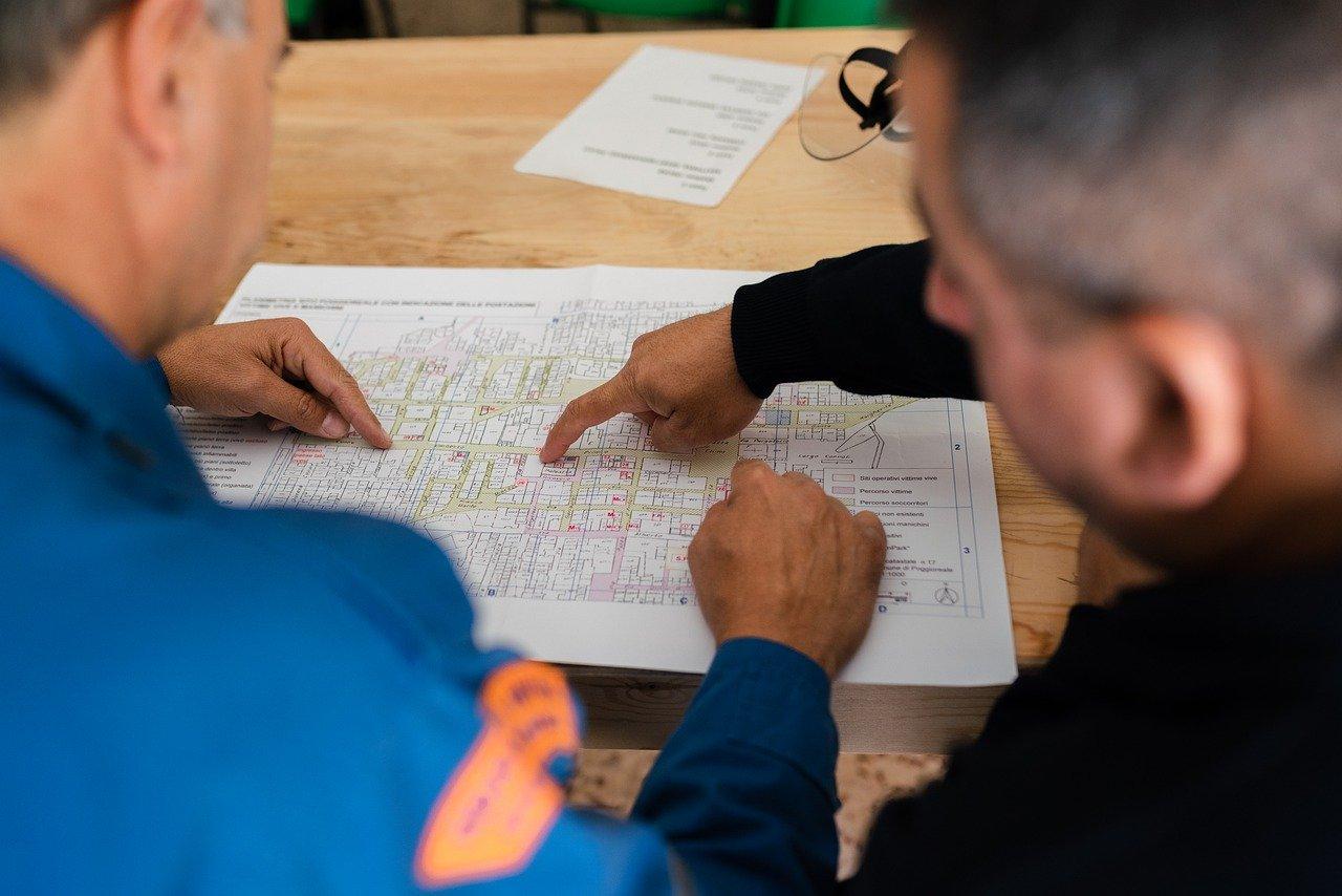 deux personnes travaillant sur un plan de conception mécanique