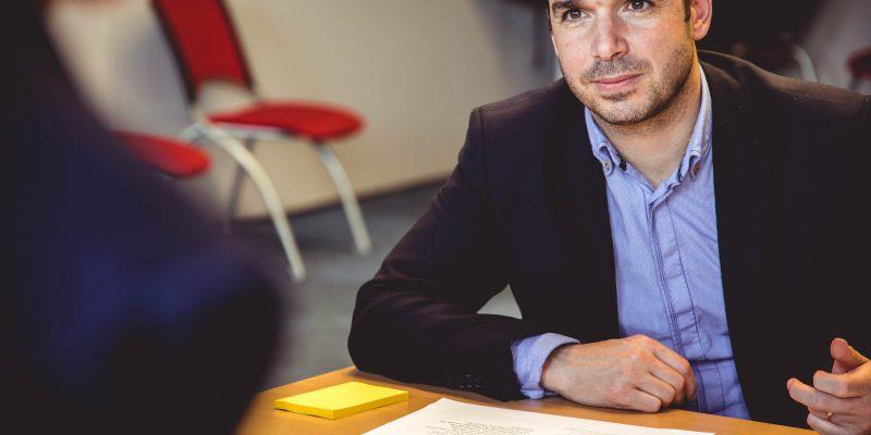 homme assis derrière un bureau avec des documents sur le bureau